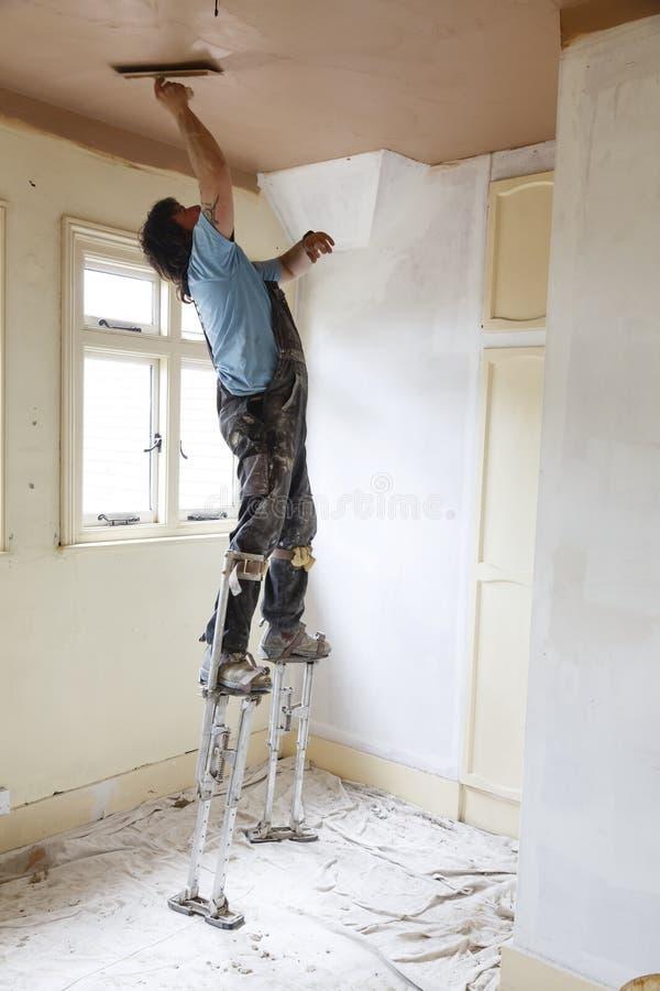 工作在高跷的石膏工 免版税库存照片