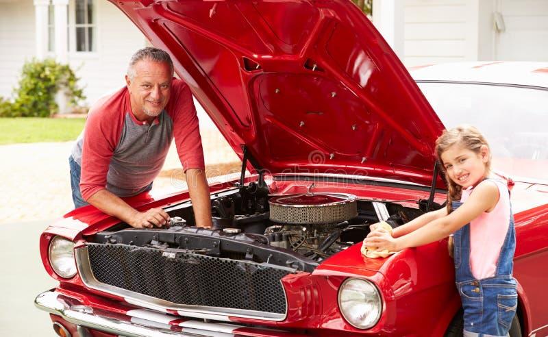 工作在经典汽车的祖父和孙女 库存照片