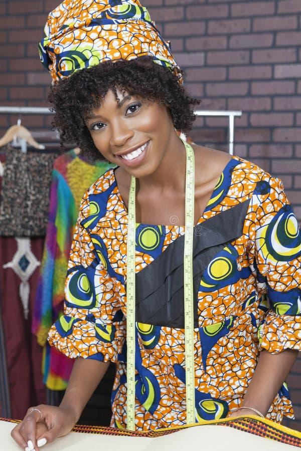 工作在织品的一位可爱的非裔美国人的女性时装设计师的画象 免版税库存图片
