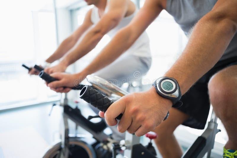 工作在锻炼脚踏车的人的中间部分在健身房 免版税库存照片