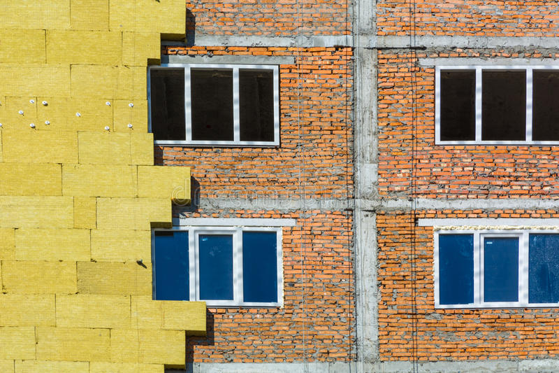 工作在玻璃棉绝缘材料外在墙壁上并且涂灰泥 免版税库存图片