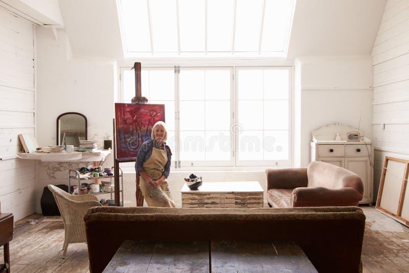 工作在绘画的女性艺术家在明亮的白天演播室 图库摄影