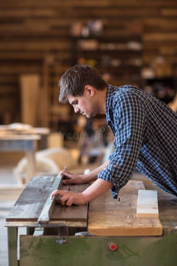 工作在他的木制品车间的熟练的木匠,使用circ 免版税库存照片
