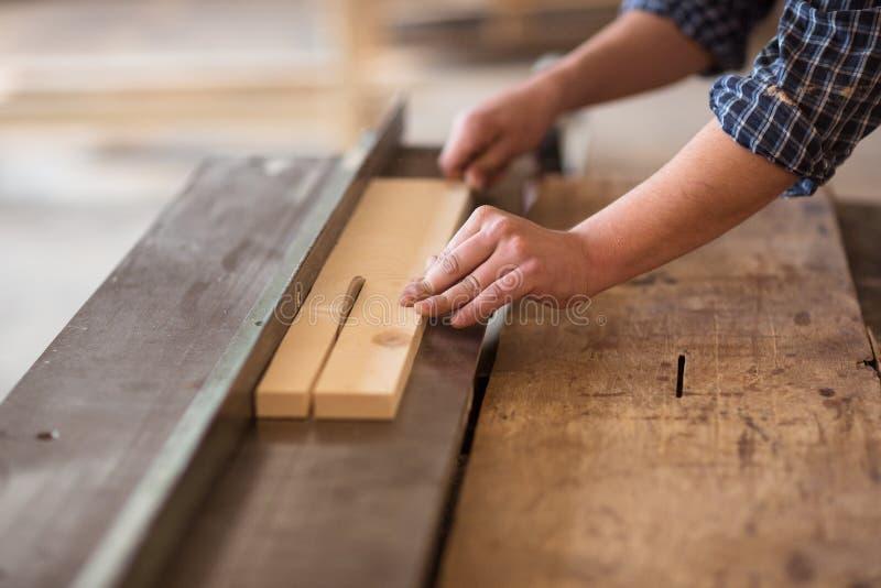 工作在他的木制品车间的熟练的木匠,使用circ 免版税库存图片