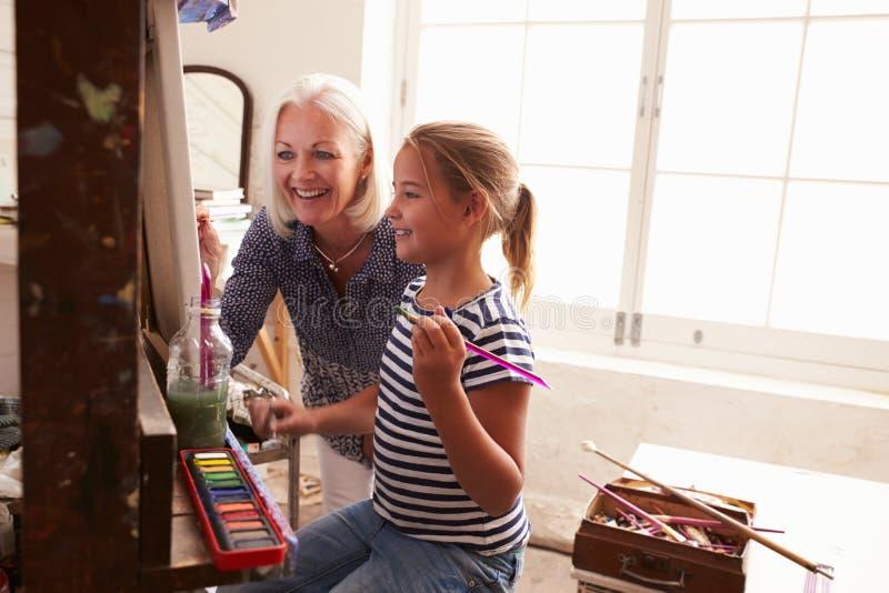 工作在绘画的母亲和女儿在艺术演播室 免版税库存图片