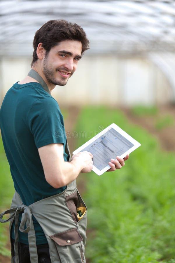 工作在他的片剂的年轻企业农夫 库存图片