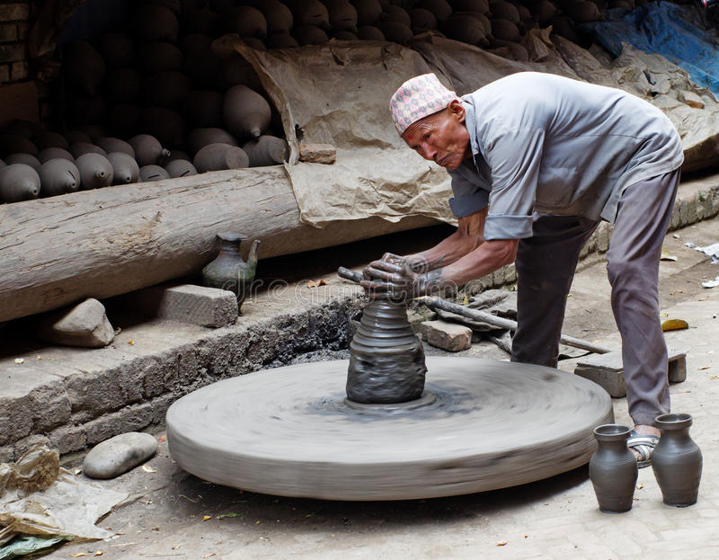 工作在他的瓦器车间的尼泊尔陶瓷工 免版税图库摄影