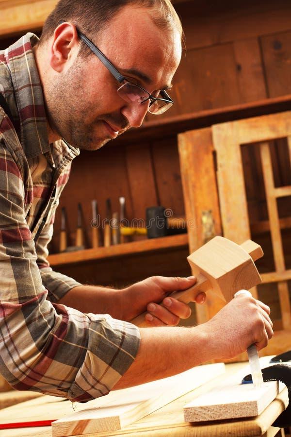 工作在他的车间的木匠 免版税库存照片