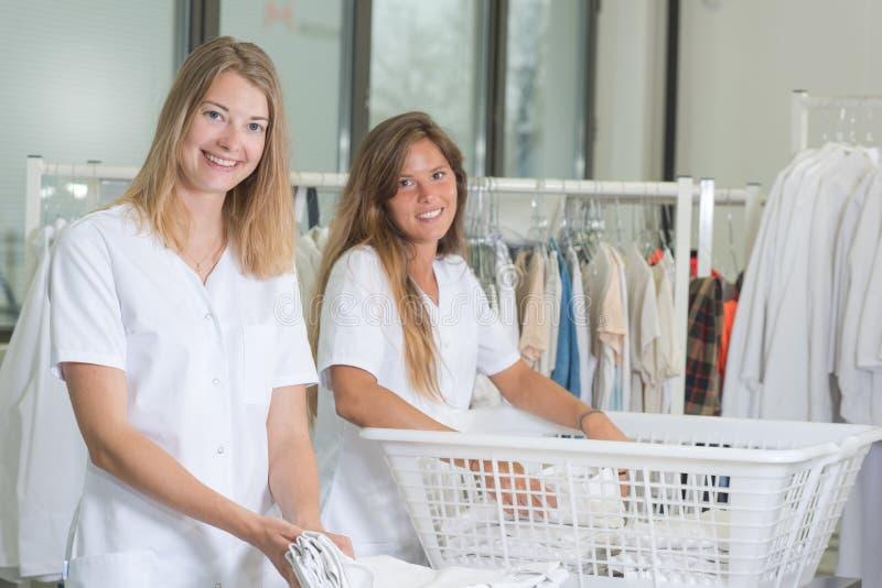 工作在洗衣店的两个夫人 库存图片