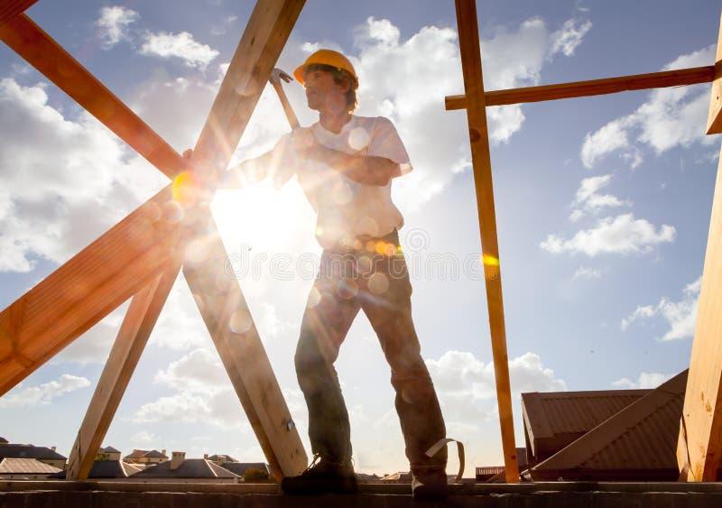 工作在建造场所的屋顶的盖屋顶的人木匠 免版税库存照片