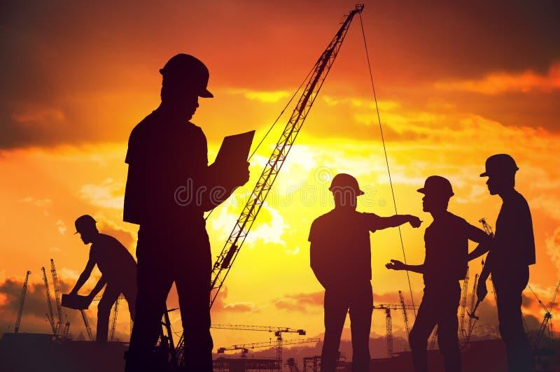 工作在建造场所的工作者剪影在suset 免版税库存照片