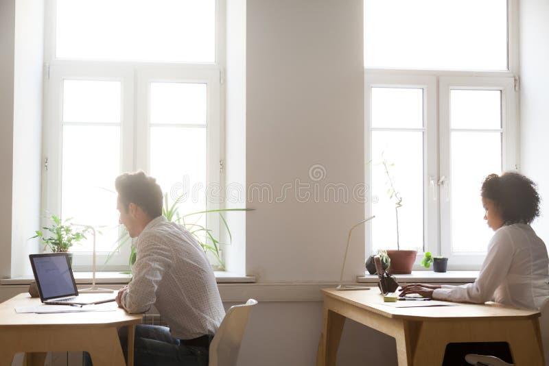 工作在coworking的空间的膝上型计算机的多种族雇员 免版税库存照片