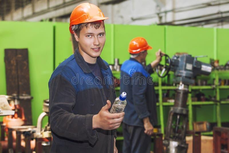 工作在equi的设施的老工厂的年轻人 库存图片