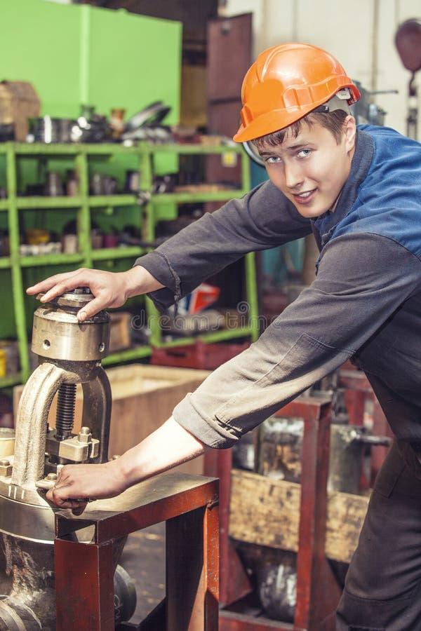 工作在equi的设施的老工厂的年轻人 库存照片