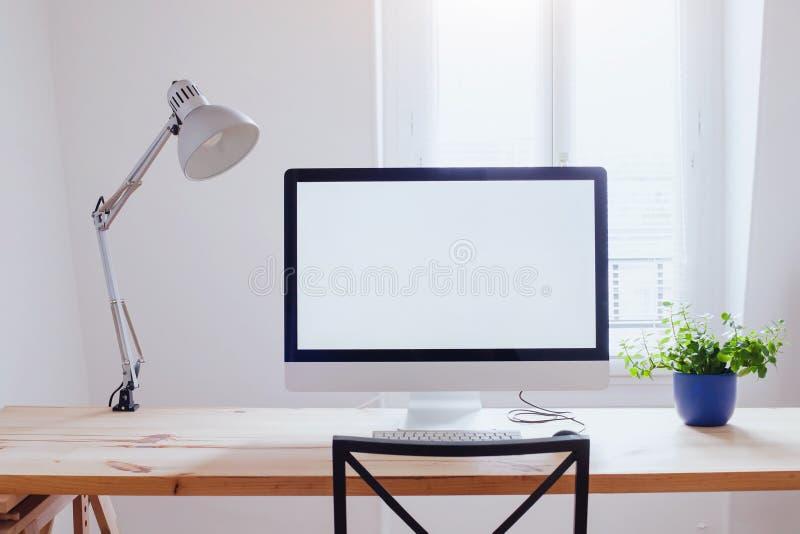 工作场所在现代美丽的办公室,有白色空的黑屏的计算机 免版税库存图片