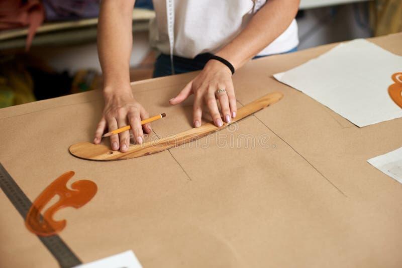 工作场所在现代设计演播室 创造专属平的纸衣物样式的女性设计师 免版税图库摄影