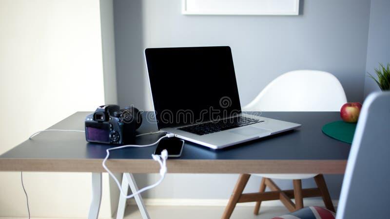 工作场所摄影师和设计师、膝上型计算机有照相机的和智能手机在桌上 免版税库存照片