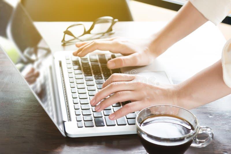 工作场所的年轻女实业家和为互联网冲浪使用一台膝上型计算机 企业网上销售的概念 免版税库存照片
