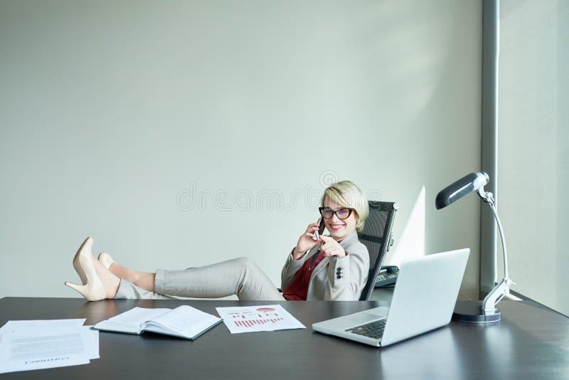 工作场所的松弛的女实业家 免版税库存照片
