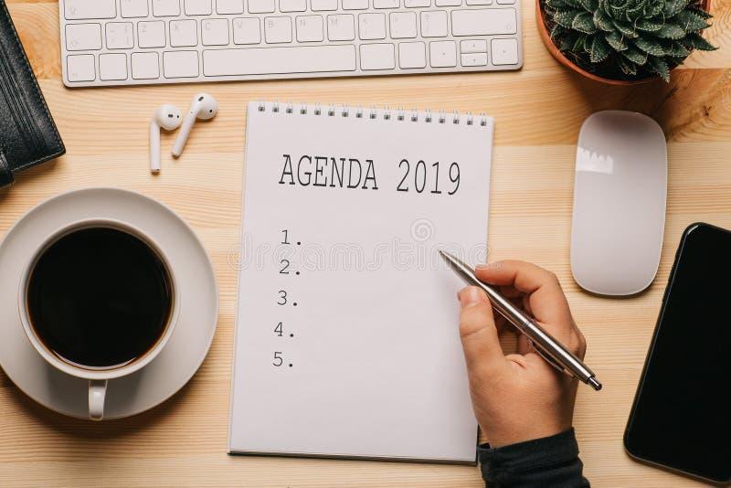 工作场所顶视图有笔记薄和文本的-在木桌,企业财务飞行的概念上的议程2019年 免版税库存图片