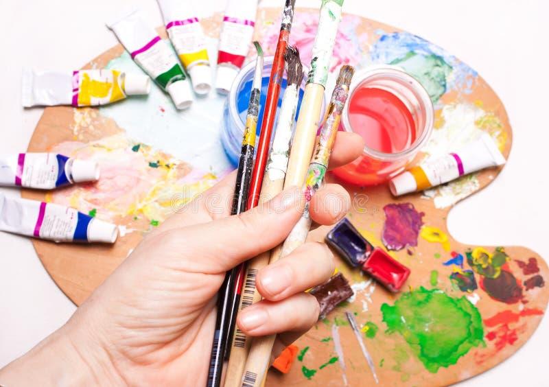 工作场所,与油漆的一张艺术家` s桌,调色板 免版税库存图片