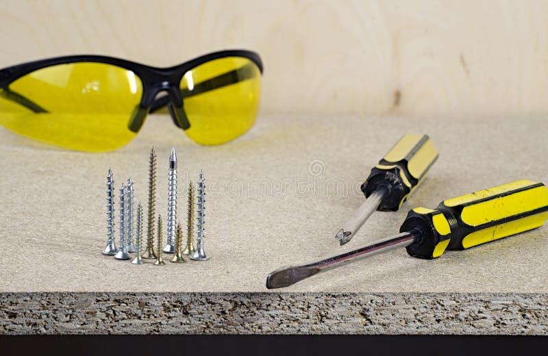 工作场所,在一张木桌上的两黄色螺丝刀和玻璃 免版税库存照片