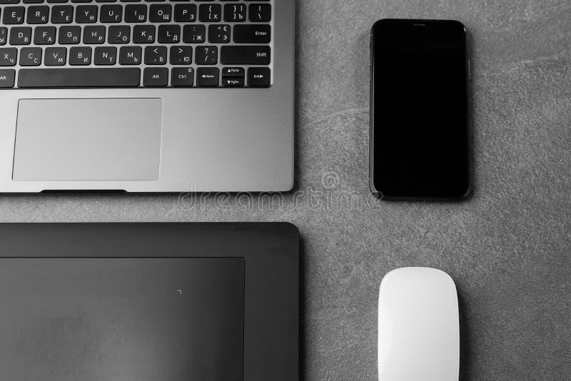 工作场所,配备带黑屏、鼠标、图形平板电脑和智能手机的开放式笔记本电脑,配备现代灰石办公桌,带角度笔记本 免版税库存照片