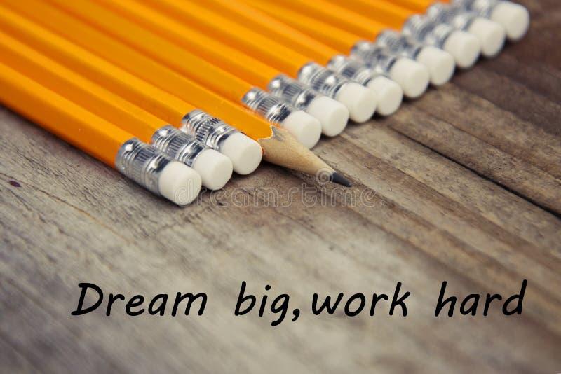 工作坚硬梦想大诱导教育消息 与黄色铅笔的土气木背景 图库摄影