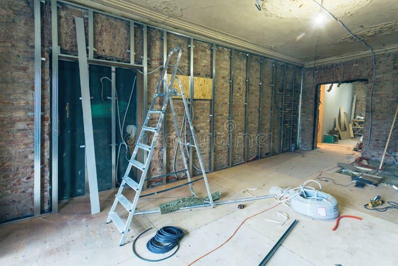 工作处理安装石膏板干式墙的金属框架做的有梯子的石膏墙壁和工具在公寓 库存图片
