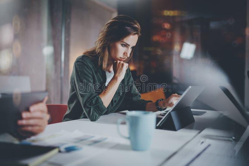 工作处理照片的工友 工作与同事一起的少妇在夜现代办公室顶楼 配合 库存图片
