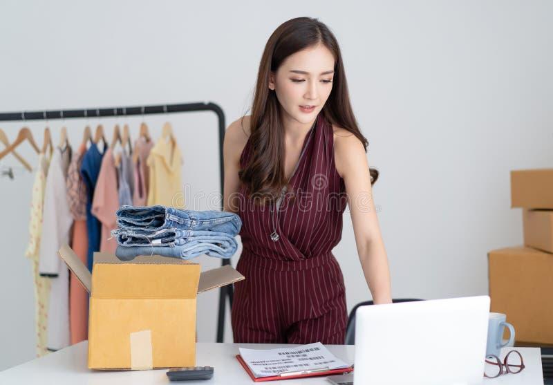 工作小企业检查她的在手提电脑的顺序和包装牛仔裤的年轻亚裔偶然妇女到纸板箱在家 免版税库存照片