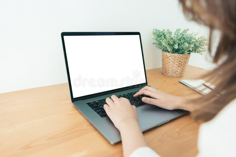 工作年轻亚裔的妇女使用和输入在有嘲笑的膝上型计算机空白的白色屏幕,当在家办公室工作区时 库存图片