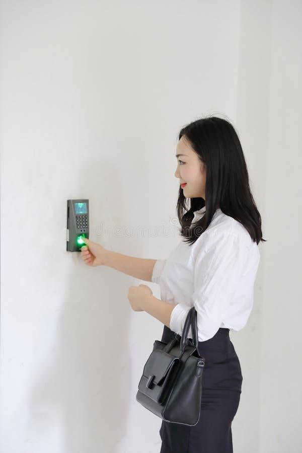 工作微笑拳打的亚洲中国办公室夫人妇女女孩在时钟指纹穿戴企业职业衣服工作场所 免版税库存照片