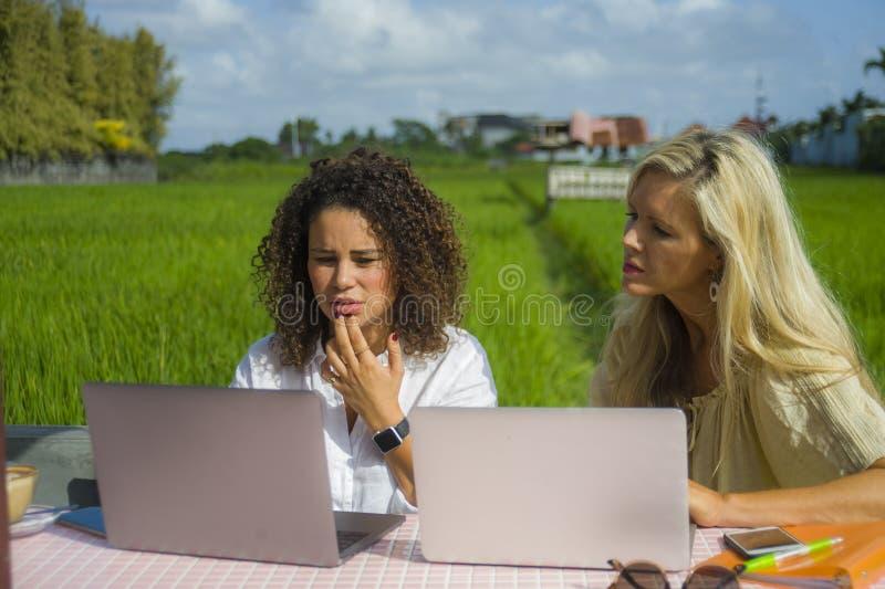 工作户外在与便携式计算机白种人妇女和一个非洲的混杂的女孩的美丽的网吧的两个愉快的女性朋友 库存照片