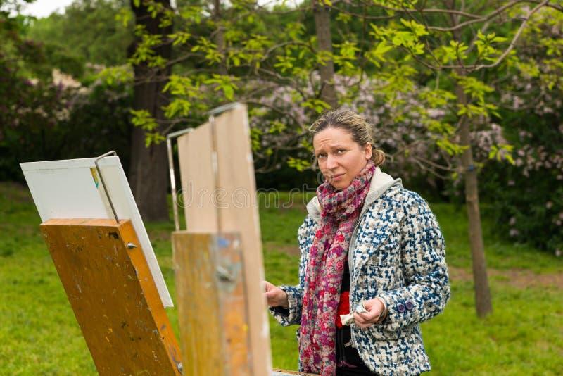 工作户外在庭院里的孤独的专业时兴的女性艺术家 免版税库存图片