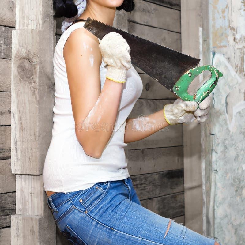 工作手套的女孩保留老锯,您需要做 没有头的躯干 免版税库存图片