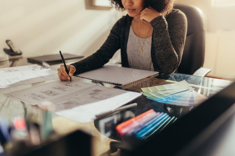 工作新的设计的女性建筑师在她工作书桌 免版税图库摄影