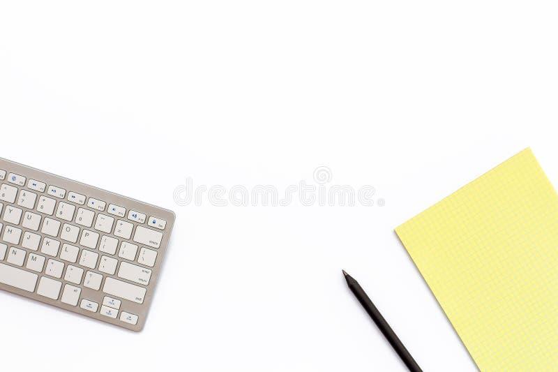 工作有键盘、一个黄色笔记薄和黑p的办公桌 库存照片