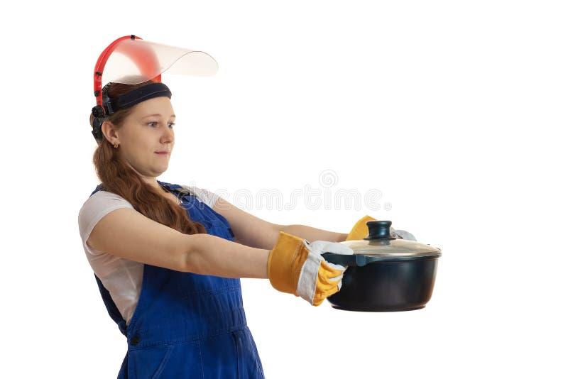 工作服和一个防毒面具的女孩拿着一个平底锅  库存照片