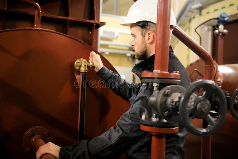 工作服的工作者和在锅炉的安全帽 免版税图库摄影