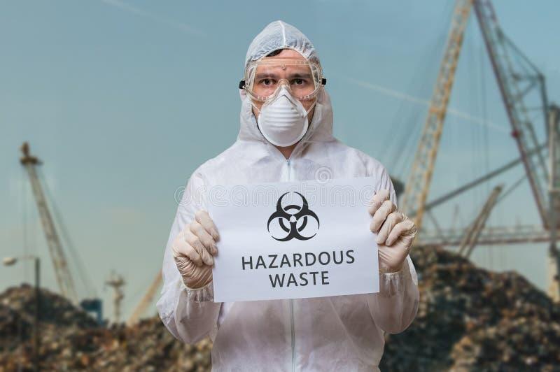 工作服的技术员在垃圾填埋对危险有害废料提出警告 免版税库存照片