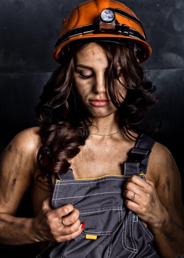 工作服的特写镜头画象性感的女性矿工工作者在他的赤裸身体,在头的盔甲有手电的 库存图片