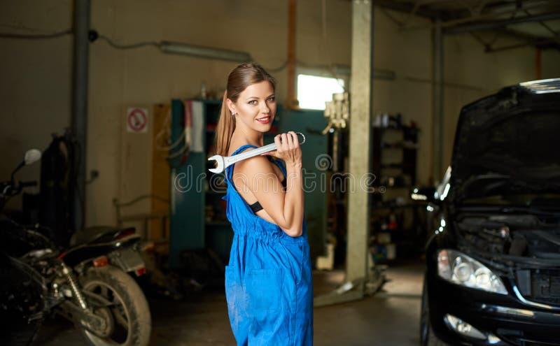 工作服的美丽的技工女孩在修理车库 库存图片