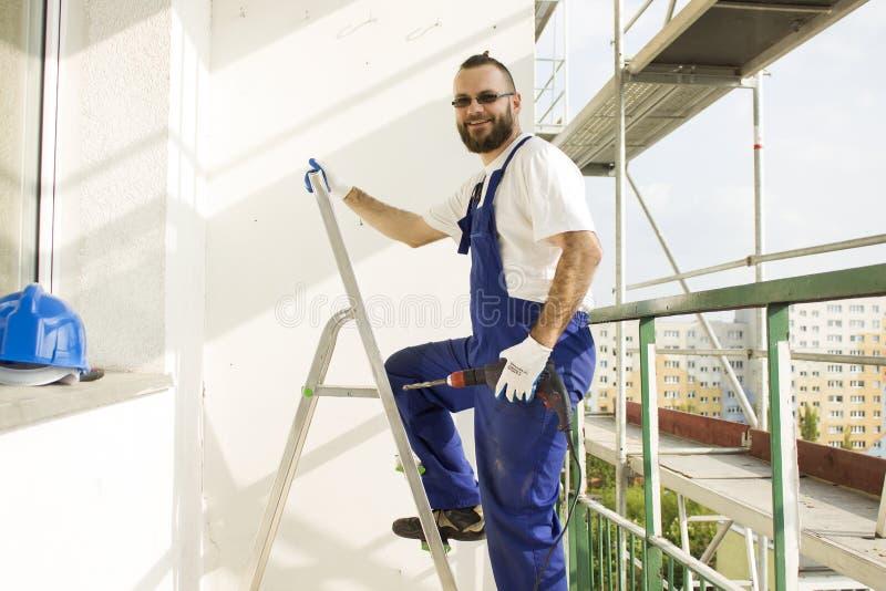 工作服装和防护手套的建筑工人在手中进入与钻子的一架梯子 免版税库存图片