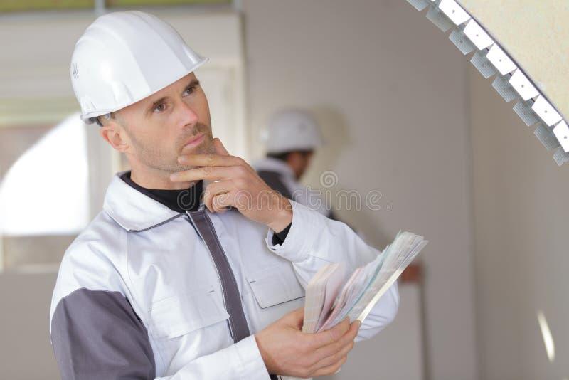 工作沉思的年轻工人户内 图库摄影
