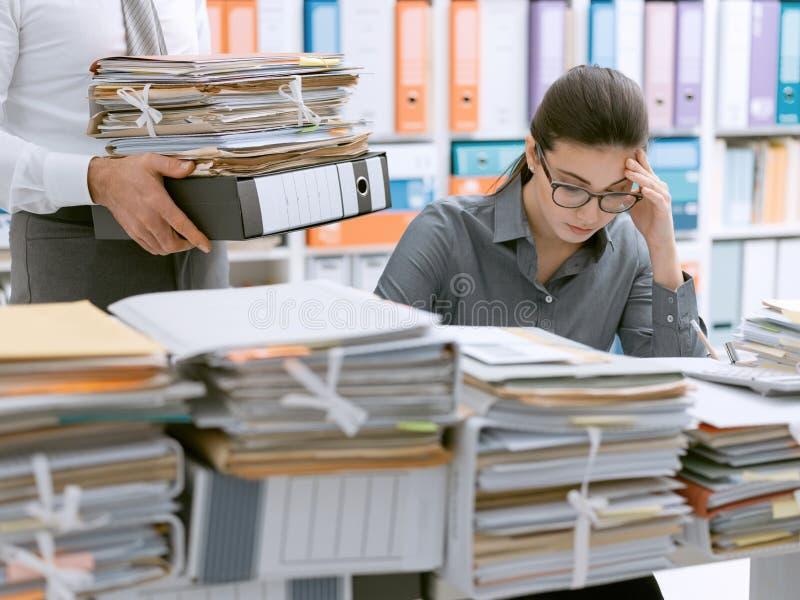 工作淹没的年轻秘书 库存照片