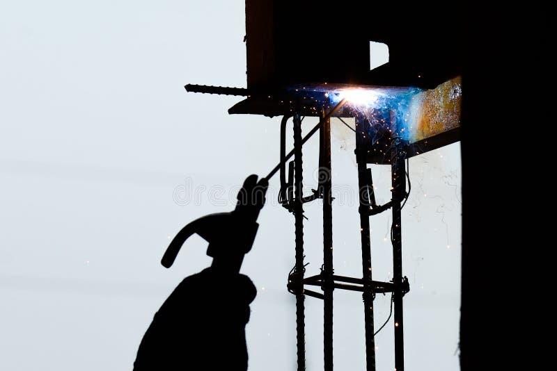 工作焊接的钢的金属工与被传播的火花和照明设备 焊接铁棍建筑的钢铁工人的手 免版税库存图片