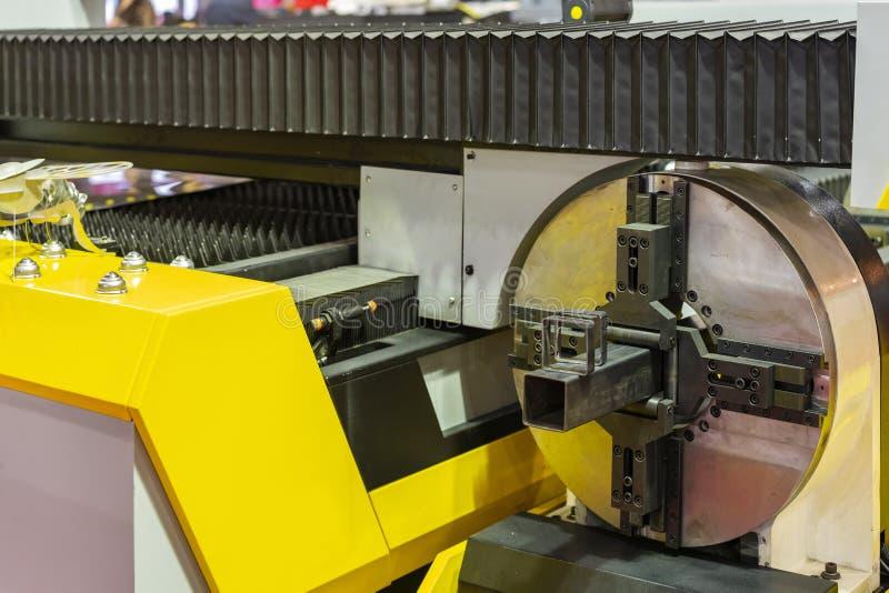 工作片断金属正方形管子的关闭在牛颈肉的钳位期间转动高精度自动激光切割机的集合  免版税图库摄影