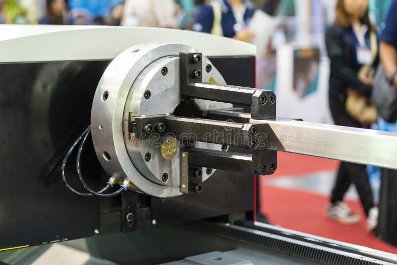 工作片断金属正方形管子的关闭在自动牛颈肉的钳位期间转动高精度自动激光切割机的集合或 免版税库存图片