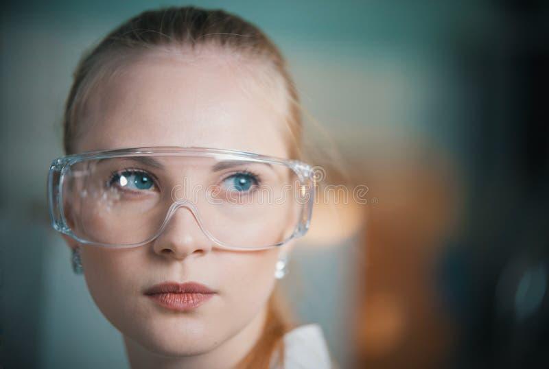 工作玻璃的一年轻女人在实验室里 免版税库存图片
